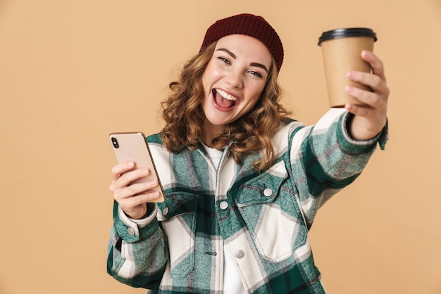 Photo of cheerful woman in knit hat using cellphone and drinking coffee takeaway isolated on beige