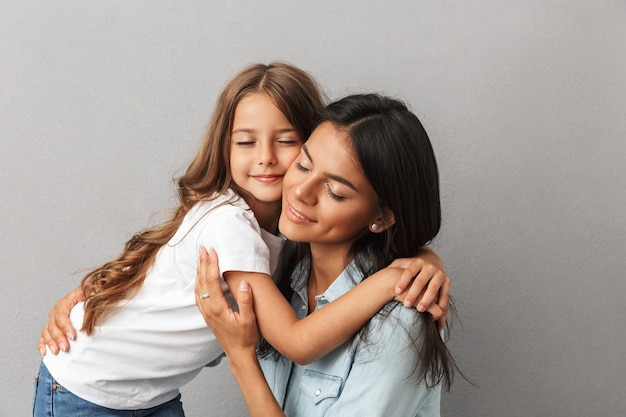 Photo of cheerful woman with little daughter smiling and hugging together, isolated over gray