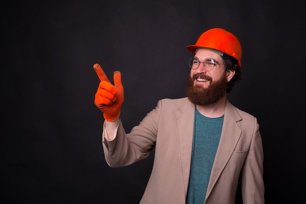 Photo of cheerful youg architect wearing gloves and hemlet and pointing away