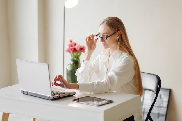 Photo of a cheerful young blonde business woman in office indoors work with laptop and mobile phone.