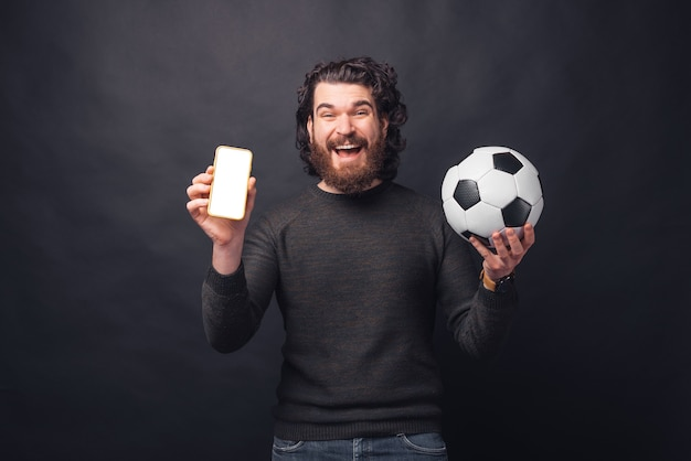 Photo of cheerful young handsome bearded man holding soccer ball and showing blank screen on smartphone
