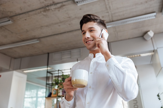 Photo of cheerful young man dressed in white shirt drinking coffee while chatting by phone. coworking. look aside.