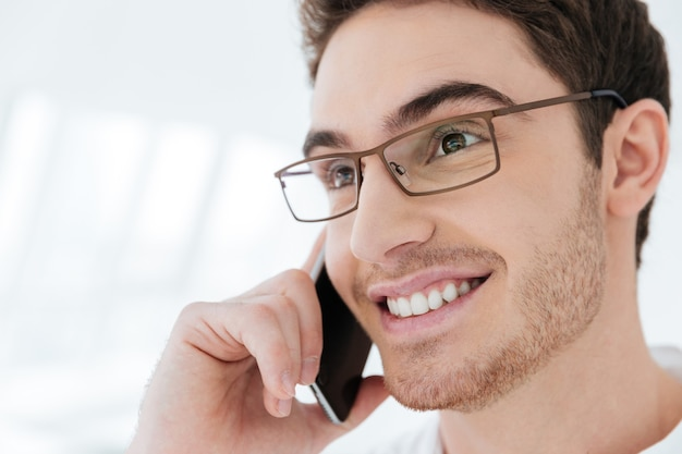 Photo of cheerful young man dressed in white shirt standing near big white window while talking by phone. look aside.