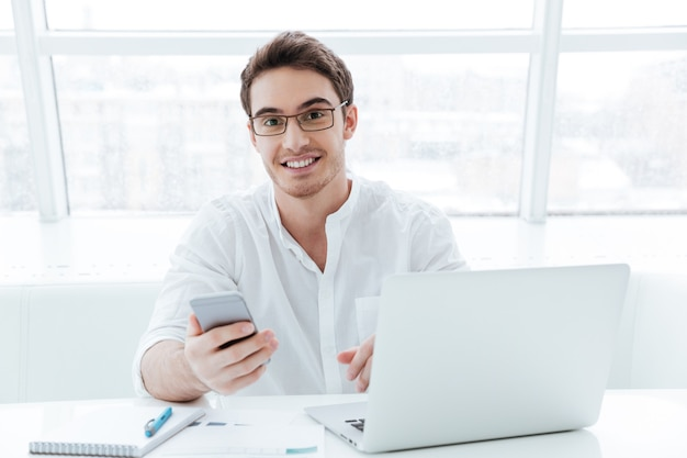 Photo of cheerful young man dressed in white shirt using laptop computer while chatting. look at camera.
