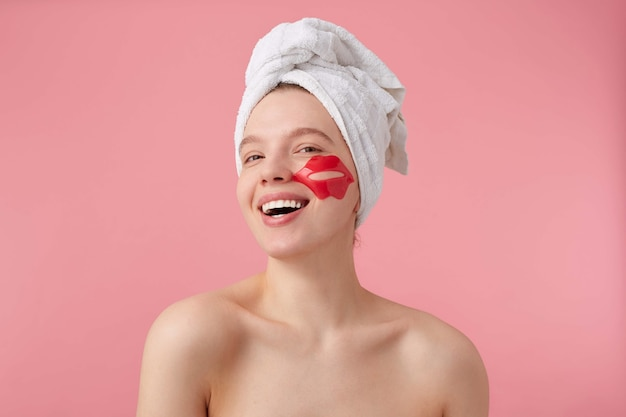 Photo of cheerful young woman after spa with a towel on her head, with patch for lips on cheeks, broadly smiles, feels so happy, stands.