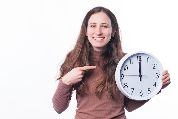 Photo of cheerful young woman pointing at round clock