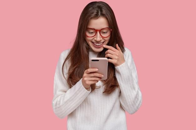 Foto di giovane donna allegra con espressione felice, tiene in mano il cellulare, controlla le notizie sui social network online, usa l'app, indossa gli occhiali e un maglione bianco