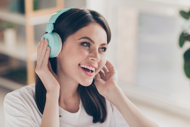 Photo of cheerful youngster girl listen stereo song with wireless blue headset in house indoors