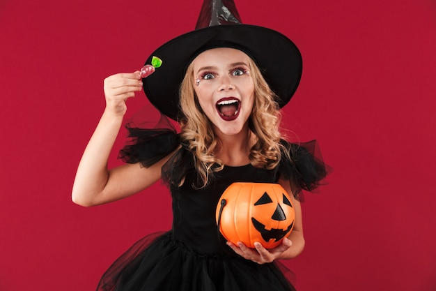 Photo of cheery little girl witch in carnival halloween costume