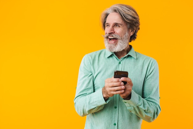 Photo of cheery positive grey-haired bearded man in blue shirt posing isolated on yellow wall using mobile phone looking aside.