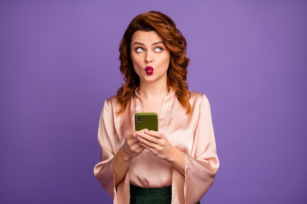 Photo of chic lady hold phone look side up empty space send shy air kisses