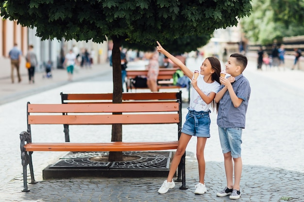 Foto di amici bambini che stanno vicino alla panchina a mangiare un gelato dolce insieme