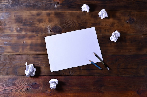 Photo of a clean white blank sheet of paper lie on a brown wooden background.