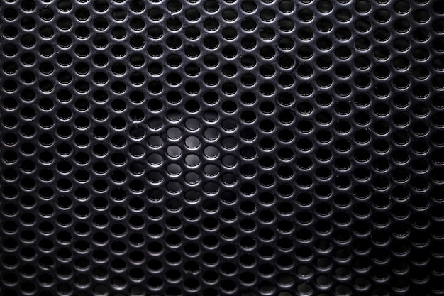 Photo of a close-up of a musical column hidden behind a grid with a pattern of rhythmically arranged holes, background image