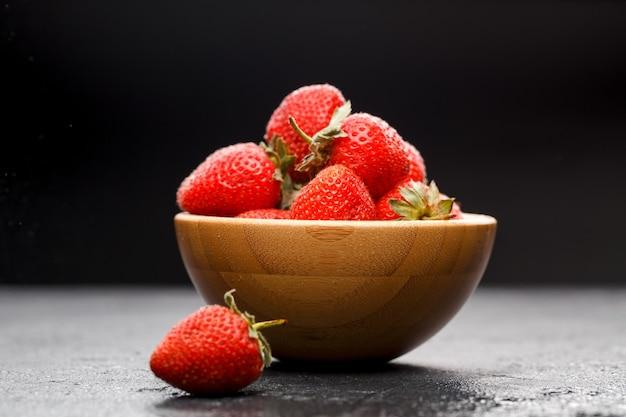 빈 검은 배경에 나무 컵에 잘 익은 딸기의 사진 클로즈업