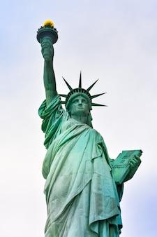 晴れた日の自由の女神と雲のある青い空の写真のクローズアップ。リバティ島。ニューヨーク、アメリカ。