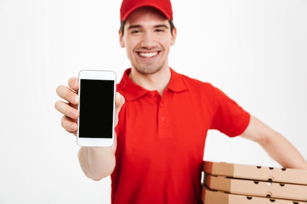 Photo closeup of affable man from delivery service in red t-shirt and cap holding stack of pizza boxes and showing copyspace screen of cell phone, isolated over white space