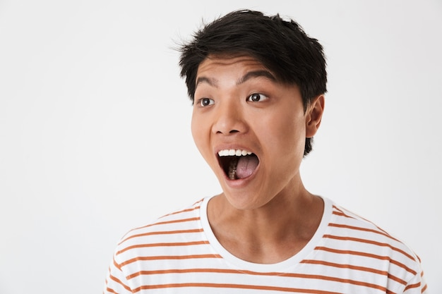Photo closeup of amazed or stunned asian man wearing striped t-shirt smiling with perfect teeth and looking aside at copyspace, isolated. concept of emotions