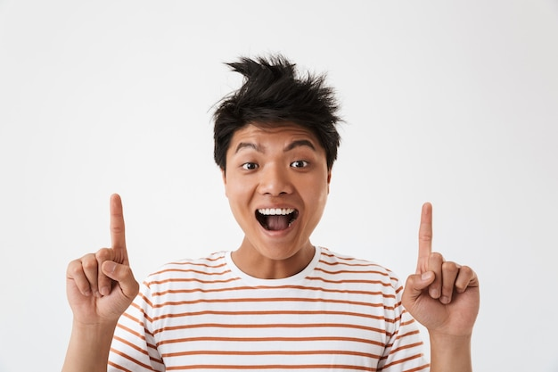 Photo closeup of chinese excited guy wearing striped t-shirt pointing fingers upward at copyspace, isolated