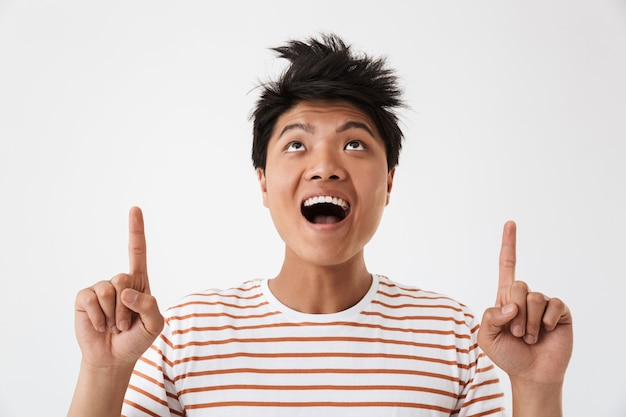 Photo closeup of chinese young man wearing striped t-shirt looking upward and pointing fingers up at copyspace, isolated