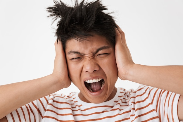 Photo closeup of confused upset asian man wearing striped t-shirt shouting and covering ears due to noise, isolated