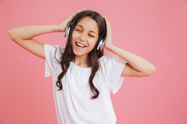 Photo closeup of cute teen girl 8-10 in casual clothing singing with closed eyes while listening to music via wireless headphones, isolated over pink background