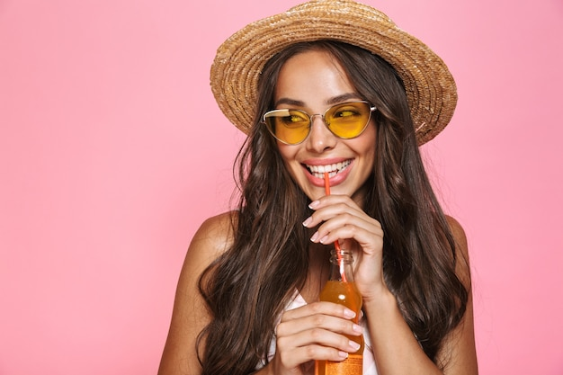Photo closeup of european woman 20s wearing sunglasses and straw hat drinking juice from glass bottle, isolated over pink wall