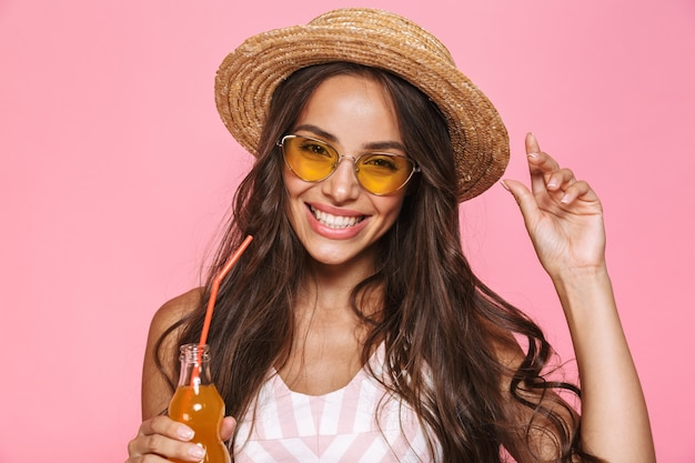 Photo closeup of fashion woman 20s wearing sunglasses and straw hat drinking soda from glass bottle, isolated over pink wall