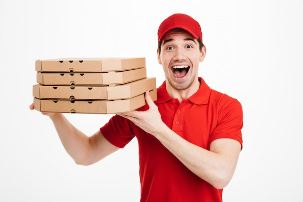 Photo closeup of handsome guy from delivery service in red t-shirt and cap holding stack of pizza boxes, isolated over white space