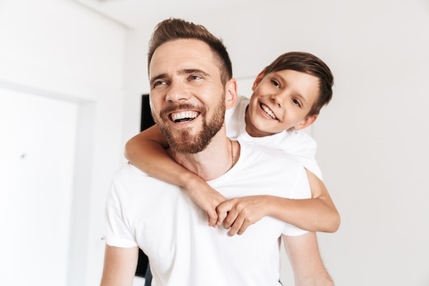 Photo closeup of happy father piggybacking his son, while resting in white bright apartment