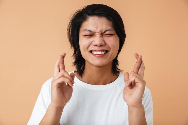 指を交差させてベージュの壁に孤立した願いを作る白いtシャツを着ているアジア人の男の写真のクローズアップ