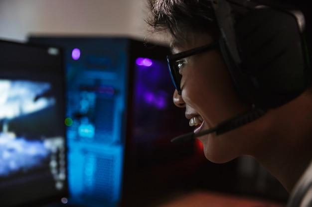 Крупным планом фото азиатского довольного мальчика-геймера, играющего в онлайн-игры на компьютере в темной комнате, в наушниках с микрофоном и использующем красочную клавиатуру с подсветкой
