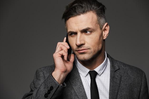 灰色の壁に分離されたオフィスで働いて、ビジネスについて電話で話しているビジネスライクな衣装に身を包んだ美しい男30代の写真のクローズアップ