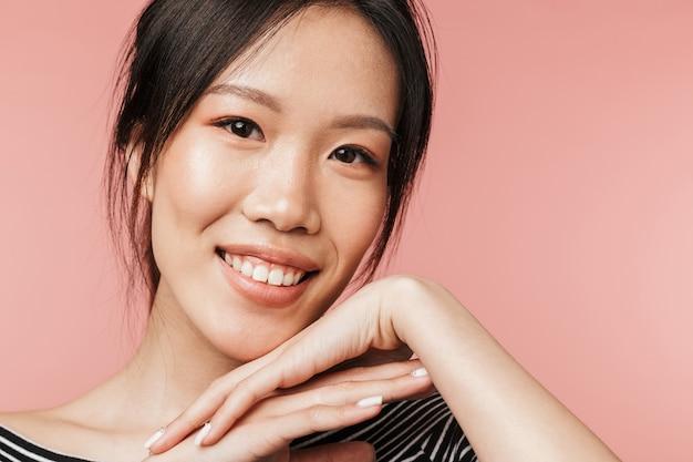 붉은 벽에 격리된 채 웃고 있는 기본 옷을 입은 매력적인 아시아 여성의 사진 클로즈업