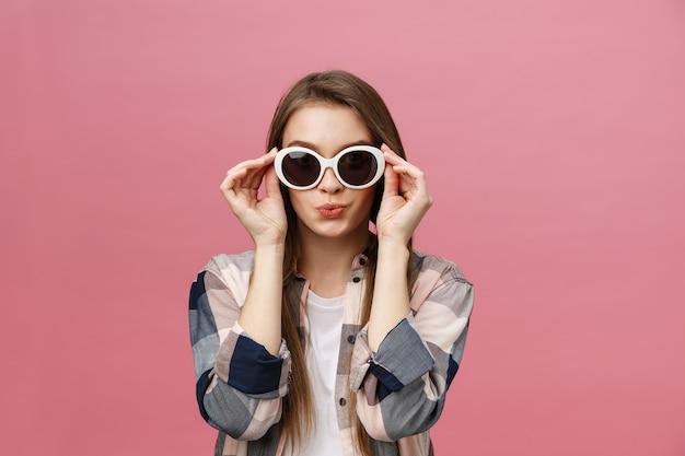 トレンディなサングラスを身に着けている長い髪型の魅力的な女性の写真のクローズアップ