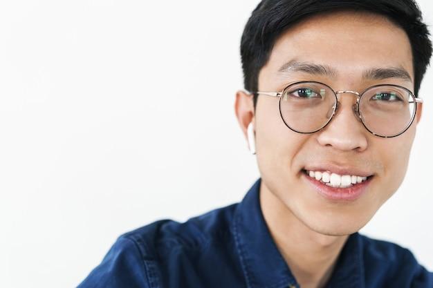 白い壁の上に孤立して笑顔のイヤポッドと眼鏡を身に着けているコンテンツ中国人男性の写真のクローズアップ