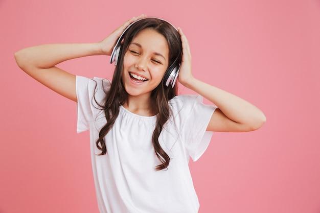 ピンクの背景で隔離のワイヤレスヘッドフォンで音楽を聴きながら目を閉じて歌うカジュアルな服を着たかわいい十代の少女8-10の写真のクローズアップ