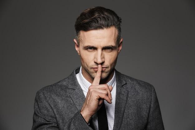 회색 벽 위에 절연 고전 의상을 입고 입술에 검지 손가락을 들고 전무 이사 남자의 사진 근접 촬영