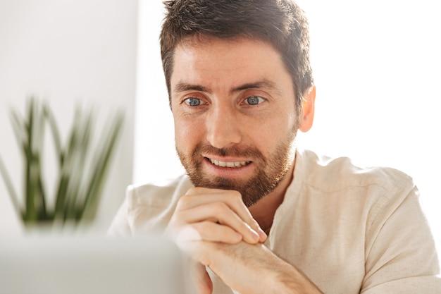 Крупным планом фото радостного бизнесмена 30-х годов в белой рубашке с помощью ноутбука, сидя за столом в современном офисе