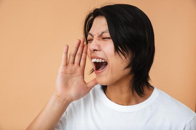 Крупным планом фото возмущенного азиатского парня в белой футболке, хмурящегося и кричащего, изолированного над бежевой стеной