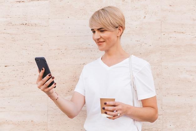 夏に屋外のベージュの壁に立って、コーヒーの紙コップを保持しながら、携帯電話を使用して白いtシャツを着ているきれいな金髪の女性の写真のクローズアップ