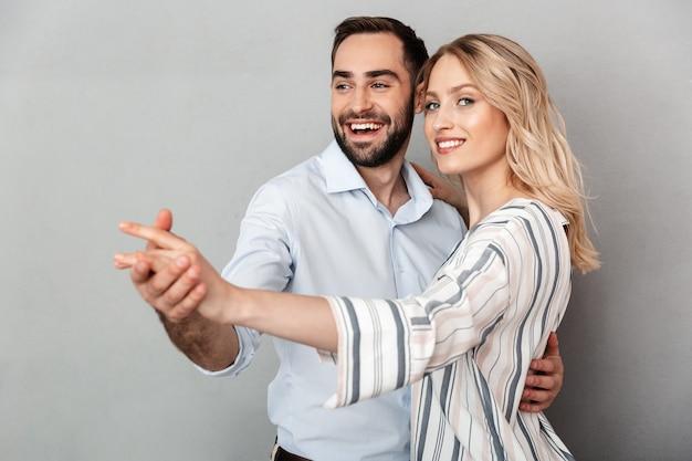 Фото крупным планом улыбающейся пары в повседневной одежде, танцующей, изолированной над серой стеной