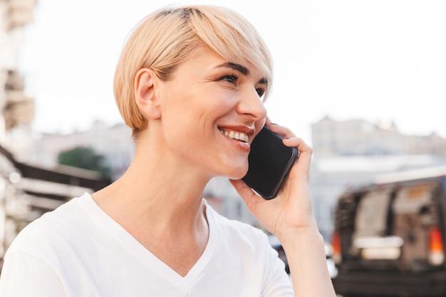 屋外の夏のカフェに座って、モバイル会話をしている白いtシャツを着て笑顔の幸せな女性の写真のクローズアップ