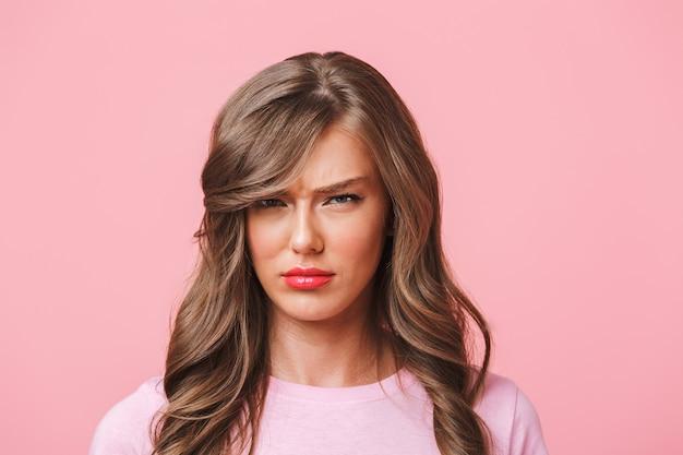 ピンクの背景に分離された基本的なtシャツのふくれっ面と憤りに眉をひそめている、長い巻き毛の動揺の女性の写真のクローズアップ