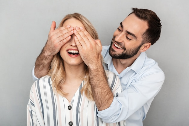 Фото крупным планом молодого человека в повседневной одежде, улыбающегося и закрывающего глаза своей подруги, изолированной над серой стеной