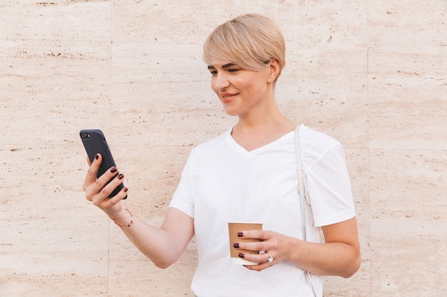 Photo closeup of pretty blond woman wearing white t-shirt using mobile phone, while standing against beige wall outdoor in summer and holding paper cup of coffee