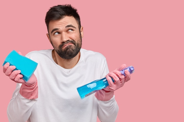 Photo of clueless unshaven man has uncertain look, frowns face, focused upwards, carries sponge and cleaning product