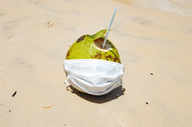 Photo of a coconut on the beach with surgical mask. pandemic and vacation concept