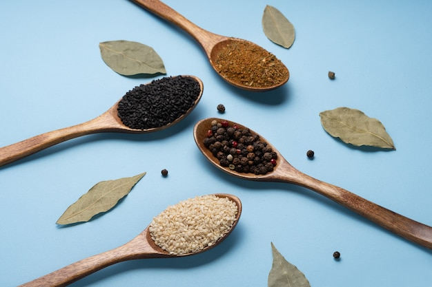 Photo collage of wooden spoons with spices on a blue background.