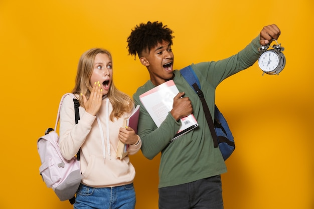 Photo of college students man and woman 16-18 wearing backpacks holding exercise books and alarm clock, isolated over yellow background